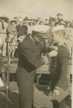 Capt O'Niel pinning medal on Billy Stamper